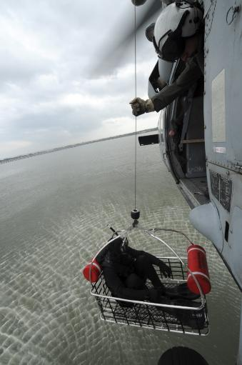 October 19, 2012 - Naval Air Crewman hoists a rescue basket into an MH-60S Sea Hawk helicopter during simulated search and rescue operations.