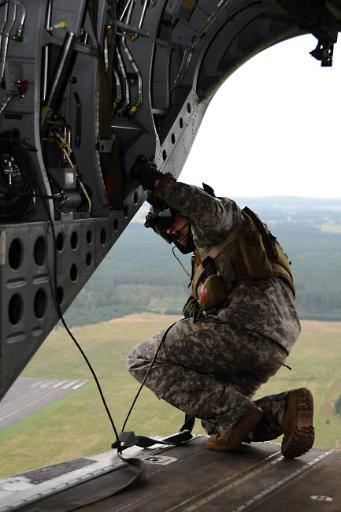 US Army crew chief checks a landing zone from the ramp of an MH-47G Chinook Poster Print by Stocktrek Images