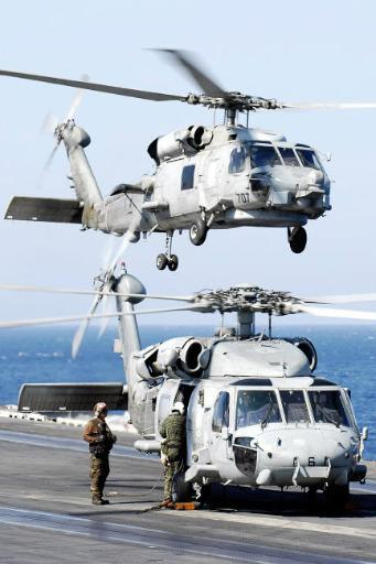 US Navy Seahawk helicopter lifting off of USS Abraham Lincoln as the aircrew of another preps for flight Poster Print by Stocktrek Images