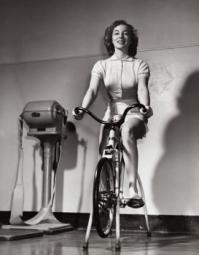 Young woman exercising on an exercise bike Poster Print SAL2553675