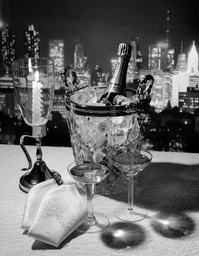 1970s Champagne Bottle In Ice Bucket With Glasses Candle & Napkins On Table & New York City Night Skyline In Background