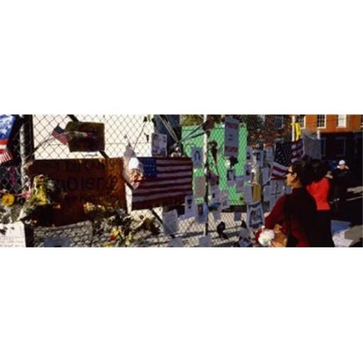 Side profile of a woman standing in front of chain-link fence at a memorial New York City New York State USA Poster Print by - 36 x 12