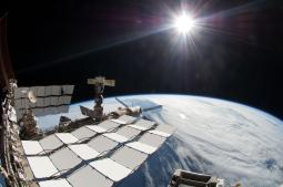 The bright sun, a portion of the International Space Station and Earth's horizon. The image was taken using a fish-eye lens attached to an electronic still camera. Poster Print PSTSTK203727SLARGE