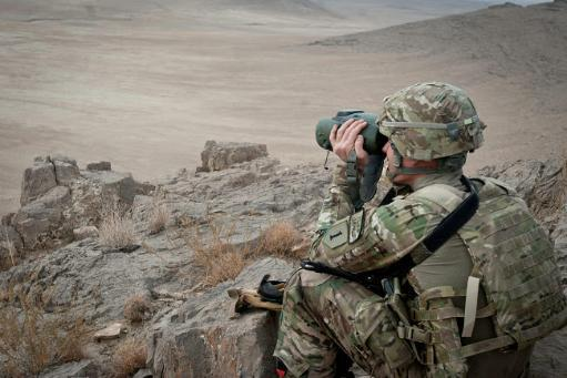 A soldier watches the impact area during a live fire exercise in Afghanistan Poster Print by Stocktrek Images