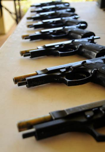 Handguns lined up on a table Poster Print by Stocktrek Images