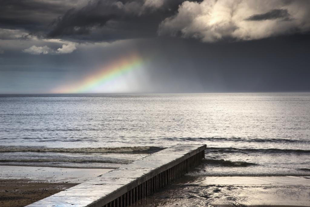 A rainbow shining in the storm clouds;Blyth northumberland england PosterPrint