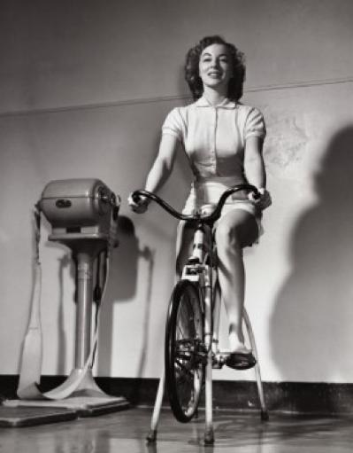 Young woman exercising on an exercise bike Poster Print