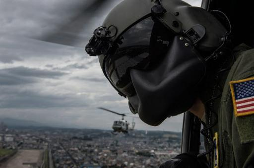 Crew chief scans the area from a UH-1N Huey helicopter Poster Print by Stocktrek Images