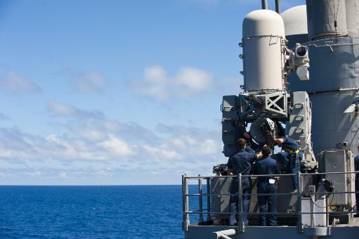 East China Sea, July 2, 2012 - Fire controlmen perform maintenance on a close-in weapon system aboard the Ticonderoga-class guided-missile cruiser.