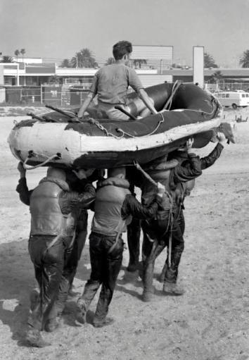 A BUD/S 1st phase boat crew carry an inflatable boat above their head with the instructor riding on top Poster Print by Michael Wood/Stocktrek Images