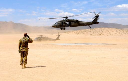 Brigade aviation officer salutes as a UH-60 Black Hawk helicopter lifts off Poster Print by Stocktrek Images