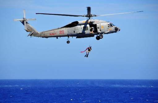 A search and rescue swimmer is lowered from an SH-60F Sea Hawk helicopter Poster Print
