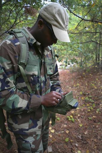 Virginia Beach, Virginia - A military technician uses a personal digital assistant in the field to wirelessly test and monitor nearby electronic.