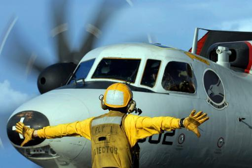 A flight deck director signals the pilot of an E-2C Hawkeye to spread his wings Poster Print by Stocktrek Images