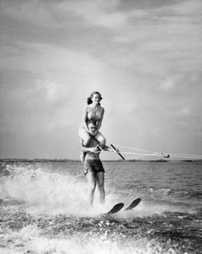 Young man waterskiing in sea with young woman sitting on his shoulders Poster Print