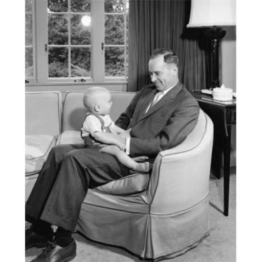 Posterazzi SAL2559783 Mid Adult Man Sitting in an Armchair Holding His Son & Smiling Poster Print - 18 x 24 in.