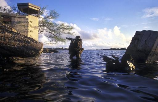 Two Navy SEALs transition from under the water and begin crossing the beach wearing Draeger LAR-V oxygen rebreathers, lifejackets and weapons at.