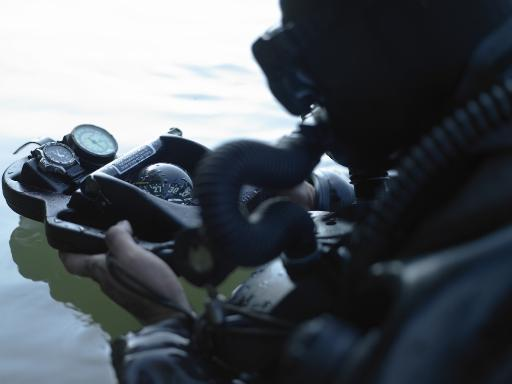 Special Forces combat diver takes a look at his compass to make sure he is on course to the target Poster Print