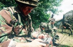 A British Army reservist inputs coordinates into a handheld GPS device Poster Print by Stocktrek Images thumbnail