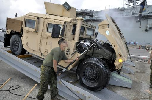April 23, 2011 - Marine aboard the amphibious transport dock ship USS Ponce, uses a pressure washer to clean the underside of a Humvee hood during.
