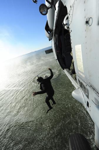 October 22, 2012 - A naval air crewman jumps from an MH-60S Sea Hawk helicopter during simulated search and rescue operations Poster Print