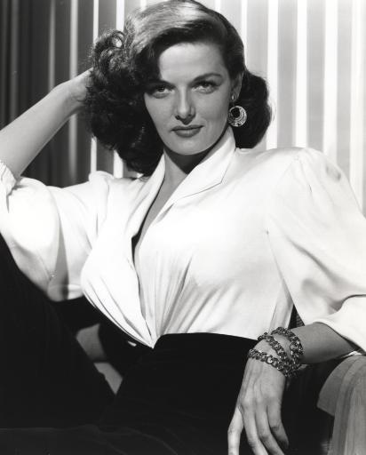 Jane Russell Posed in White Linen V-Neck Dress and Black Linen High Waist Pants with Layered Hoop Earrings while Right Hand Placed Behind the Head.