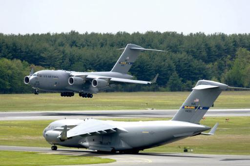 A C-17 Globemaster III performs touch and go landings while another prepares for take-off Poster Print by Stocktrek Images
