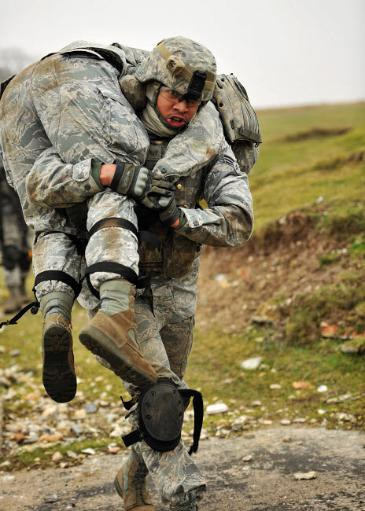 A soldier transports a fellow wounded soldier using the fireman s carry technique Poster Print by Stocktrek Images