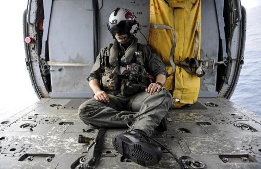 Arabian Sea, August 29, 2013 - A search and rescue swimmer sits in the back of an MH-60S Sea Hawk helicopter. Poster Print
