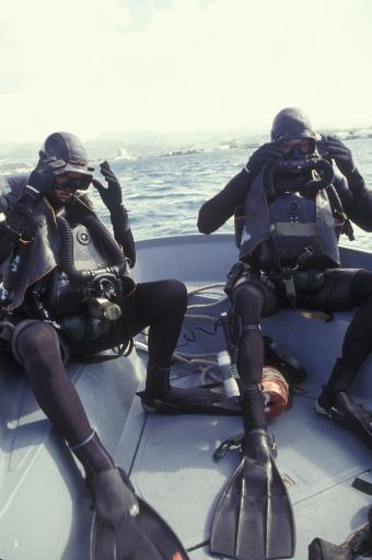 Navy SEALs combat swimmers donn their equipment in a utility boat Poster Print