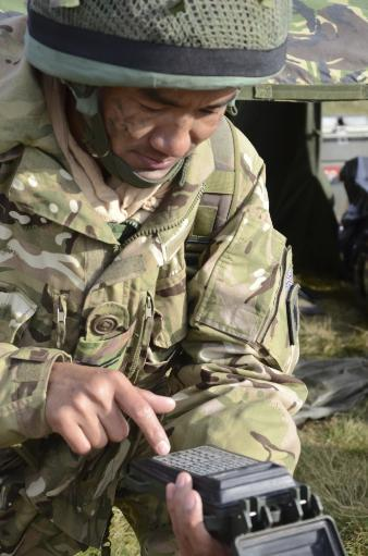 A soldier inputs the firing data into a handheld device Poster Print