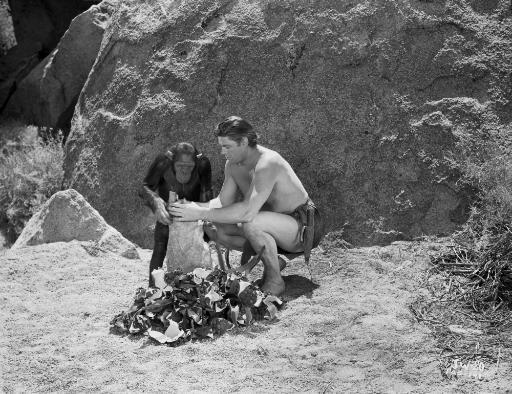 Johnny Weissmuller Filling the Sack with the Help of His Monkey in a Classic Movie Scene Photo Print O8WA7BBJ0SCDSBZW