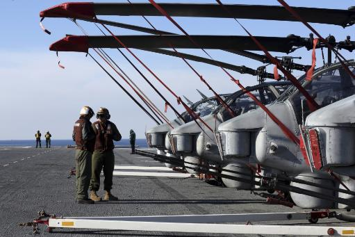 Atlantic Ocean, January 23, 2013 - Marines stand next to a row of AH-1N Cobra helicopters on the flight deck of the amphibious assault ship USS.