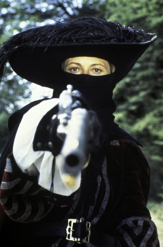 A publicity still of Faye Dunaway wearing a historical costume and carrying a gun Photo Print