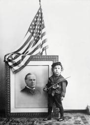 Boy in sailor uniform standing by a portrait of William McKinley Poster Print by Stocktrek Images PSTSTK500620A