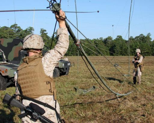 Marines raise an OE-254 field radio antenna during a communications exercise Poster Print by Stocktrek Images