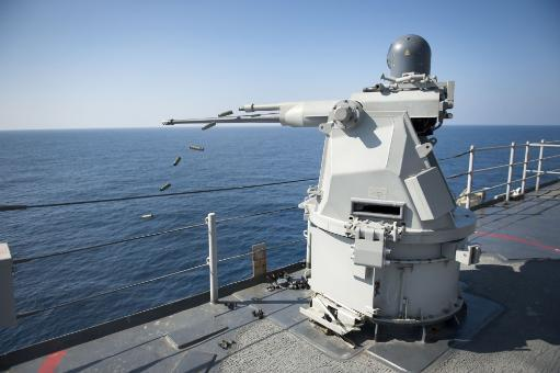Pacific Ocean, December 31, 2011 - A Mk 38 MOD 2 25mm machine gun system aboard the amphibious dock landing ship USS Pearl Harbor ejects casings.