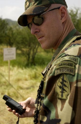 Special forces soldier enters coordinates into his GPS device Poster Print by Stocktrek Images