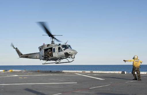 Atlantic Ocean, January 31, 2012 - A sailor directs a UH-1N Huey helicopter during flight operations aboard the amphibious transport dock ship USS.