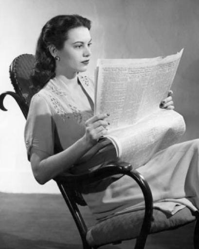 Young woman sitting on a rocking chair reading a newspaper Poster Print Z8S8YDEHFJFOISUU
