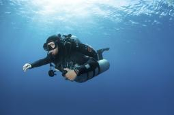 Technical diver with equipment swimming in clear blue water Poster Print PSTKWD400121U