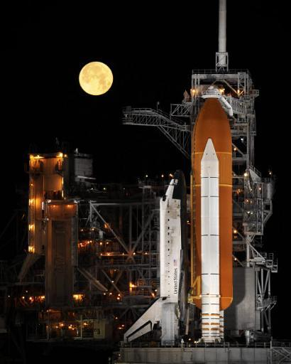 A nearly full Moon sets as Space Shuttle Discovery sits atop the launch pad Poster Print by Stocktrek Images