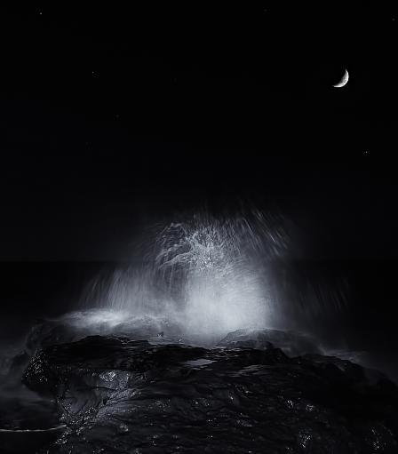 The crescent moon and waves splashing over rocks in Miramar, Argentina Poster Print