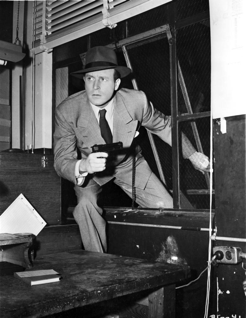 A Publicity Still Of Lawrence Tierney Climbing through A Window Photo Print