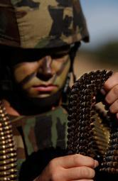 Airman loads up ammunition for the M-249 automatic rifle Poster Print by Stocktrek Images