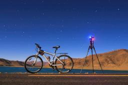 A camera, tripod and bicycle on a full moon night at Yamdrok Lake, Tibet, China Poster Print by Jeff Dai/Stocktrek Images PSTJFD200045S