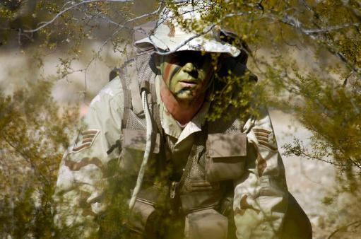 A soldier practices evasion maneuvers during a combat survival training course Poster Print by Stocktrek Images
