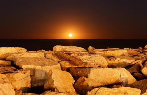 The moon rising behind rocks lit by a nearby fire in Miramar, Argentina Poster Print