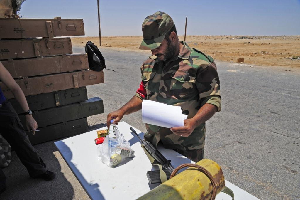 A rebel collects his food ration at a checkpoint in Ajdabiya, Libya. A war betwean Gaddafi army and Libya's Transitional National Council army with air support from NATO started on March 17, 2011. Poster Print