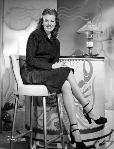 Janis Paige sitting on a White Chair in Black V-Neck Long Sleeve Linen Shirt and Black High Heel Shoes with Hands on the Lap Photo Print